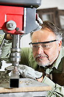 Close-up of mature man wearing protective eyewear concentrating on work