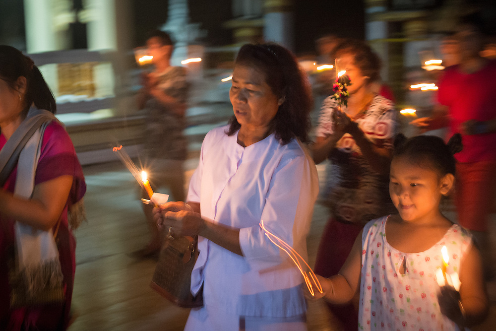 Devotees 'wien tien' (Walk round the Temple's main chapel 3 times with a candle, lotus flower and incense sticks) in Nakhon Nayok, Thailand.