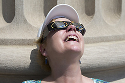 August 21, 2017 - Washington, District of Columbia, USA - ANNE HOPEWELL of Washington, D.C. watches the 2017 Solar Eclipse through her eclipse glasses on the steps of the National Archives Building. (Credit Image: © Alex Edelman via ZUMA Wire)