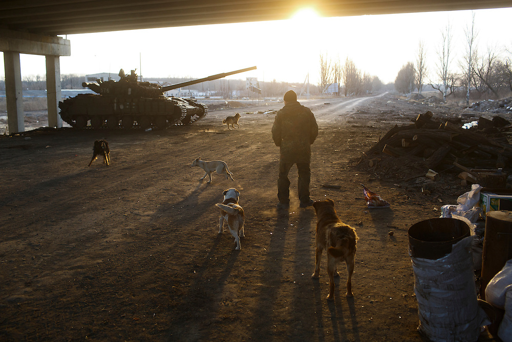 A volunteers with Dnipro-1 battalion walks under the bridge as the sun rises on March 20, 2015 near Pisky, Ukraine.
