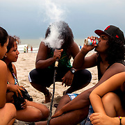 QUEENS, N.Y. - JULY 2, 2015: A group of friends smokes from a hookah that is buried in the sand at Rockaway Beach on a Thursday before the long Fourth of July holiday weekend. CREDIT: Sam Hodgson for The New York Times