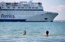 © Licensed to London News Pictures. 23/08/2019. Portsmouth, UK. Swimmers take to the sea as a ferry passes at Southsea, Portsmouth. Record high temperatures are expected in parts of the United Kingdom over the three day bank holiday weekend. Photo credit: Peter Macdiarmid/LNP