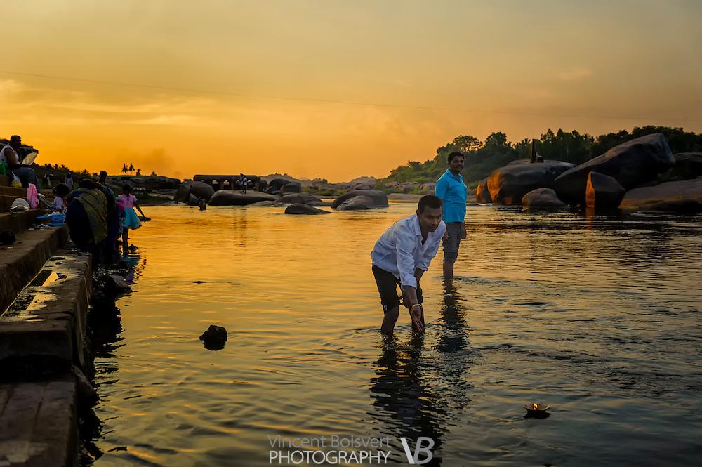 Hindu pilgrims placing floating candles on the Tungabhadra river near Hampi, India