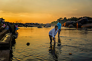 Hindu pilgrims placing floating candles on the Tungabhadra river near Hampi, India