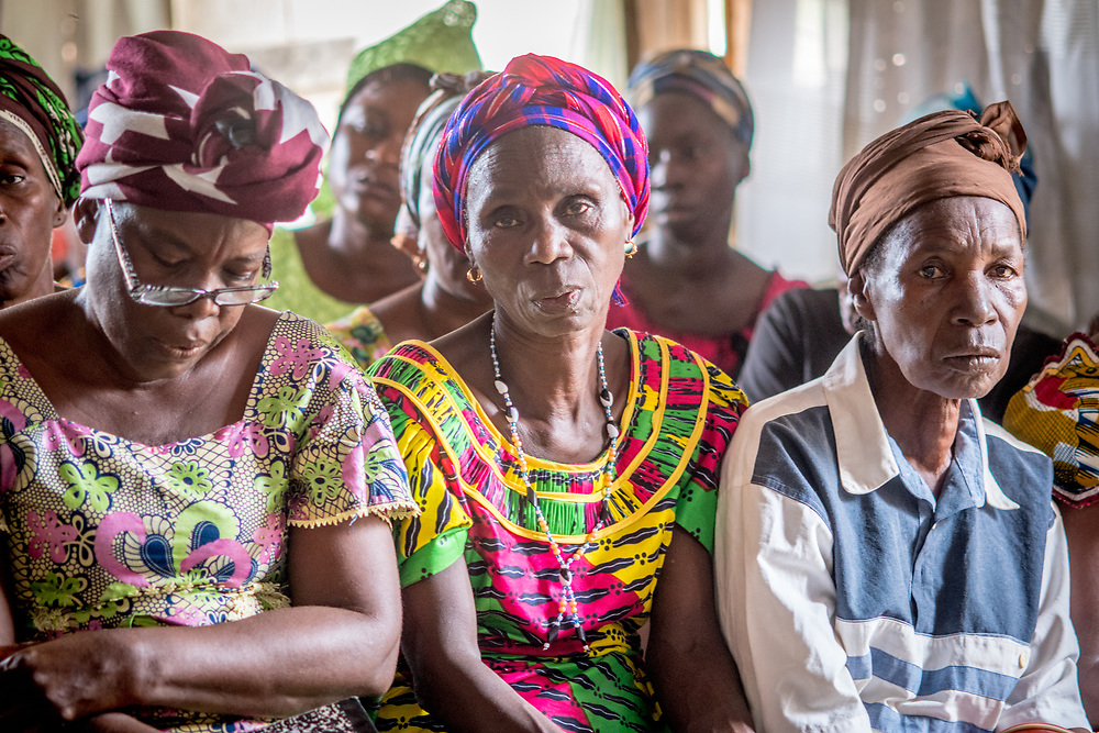 Two older women look intently at the camera amongst other women in a church congregation in Ganta, Liberia