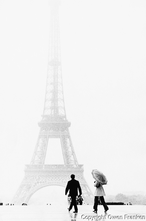 Paris, France --- Man and Woman Walking near Eiffel Tower --- Image by © Owen Franken