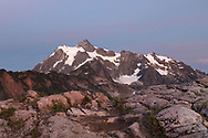 After sunset light on Mt. Shuksan from the Artist Point to Huntoon Point trail along Kulshan Ridge in Washington State's North Cascades Range. Photographed from Huntoon Point in the Mount Baker Wilderness. Mount Shuksan itself lies in North Cascades National Park.