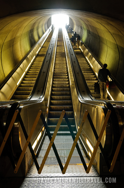 A Washington DC Metro escalator is out of service . . . again . . . and barricaded off to prevent passengers from using the center row. At the top is the bright daylight at the entrance to the station.