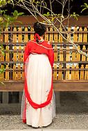 A woman in traditonal Japanese dress looking at prayer boards at the Fushimi Inari Shrine, Kyoto, Japan