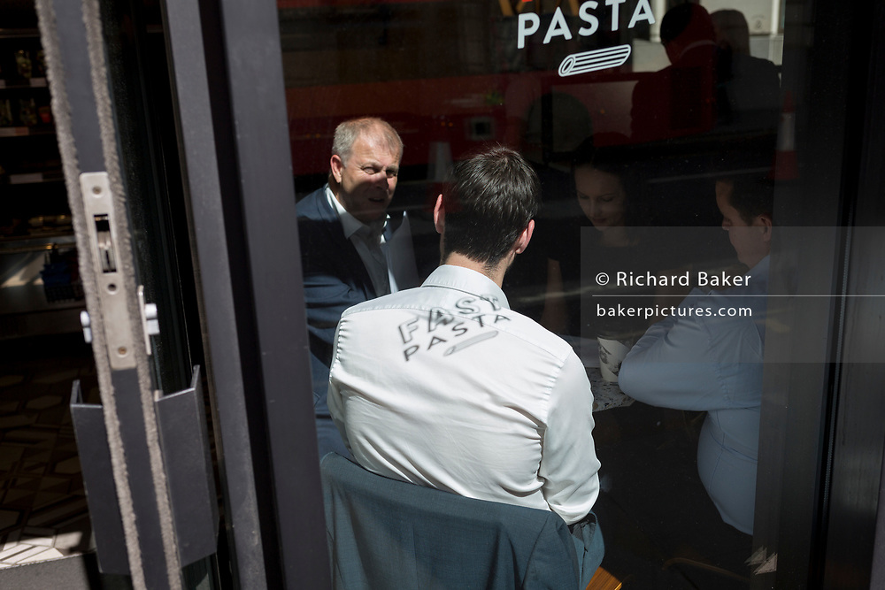 Colleagues and associates meet in the window of a cafe in the City of London - the capital's financial district, on 6th June 2018, in London, England.