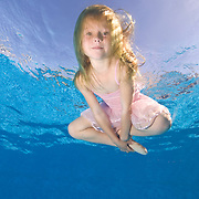 6 year old girl practicing ballet underwater in swimming pool  MR
