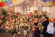 New York, NY, October 31, 2013. A woman and a boy in front of the public altar in a tent outside St. Mark's Church-in-the-Bowery on New York City's lower East Side. The black and white illustrations on the back wall are replicas of illustrations by José Guadalupe Posada, creator of the catrina, the woman's skull seen on the left.