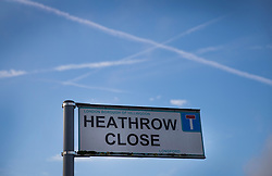 "© Licensed to London News Pictures. 27/10/2016. London, UK. Aircraft vapour trails are seen over a road sign for Heathrow Close - a residential street in the village of Longford near Heathrow Airport. The government has announced that a third runway will be built at the United Kingdom's busiest airport. The Cabinet are divided - with Foreign Secretary Boris Johnson saying that the project is ""undeliverable"". Conservative MP for Richmond Zac Goldsmith has resigned. Photo credit: Peter Macdiarmid/LNP"
