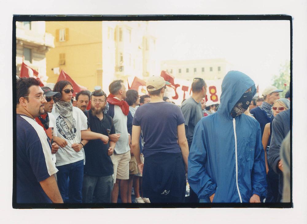 Proteste contro il summit del G8, Genova luglio 2001. Corteo di sabato 21 luglio. Strani personaggi col volto coperto si dispongono lungo tutto il corteo, e sfilano con i manifestanti pacifici. In questa immagine, uno dei personaggi travisati viene osservato con preoccupazione da un gruppo di militanti di Rifondazione Comunista. Di lì a poco, il corteo sarà attaccato dalle forze di polizia in piazzale Kennedy, dietro al pretesto della reazione a provocazioni e devastazioni da parte del Black Block. Il secondo spezzone ed i piccoli gruppi di manifestanti dispersi per le strade di Genova saranno attacati e rastrelati nelle strade circostanti. A sua volta, lo spezzone di testa del corteo sarà bolccato da azioni dei Black Block e attaccato alle spalle dalle forze di polizia.