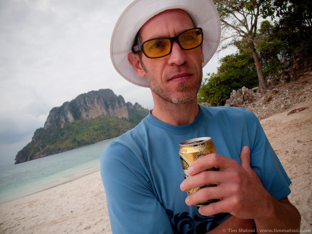 A caucasian man with a beer on the beach in Thailand.
