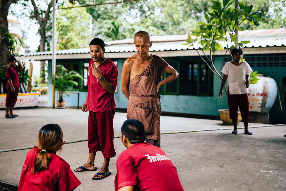 A monk oversees drug addicts in the rehab program during the ritual drinking and vomiting session at Tham Krabok temple in Saraburi, Thailand.