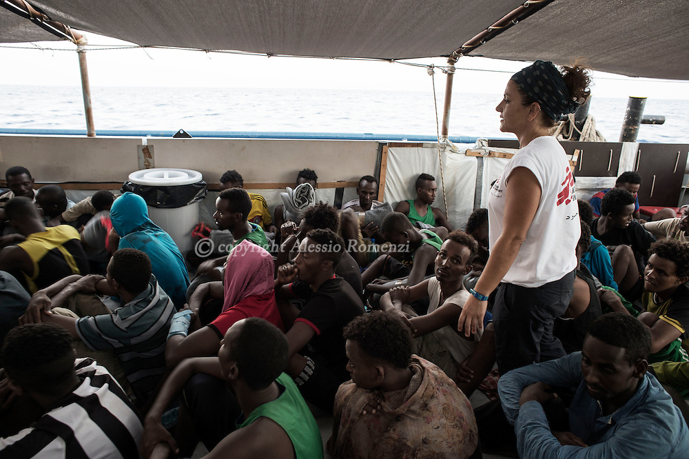Italy: MSF Dignity1: African migrants rescued at sea on the main deck of the Dignity1 and MSF field coordinator Francesca Mancia (standing) on August 23, 2015. Alessio Romenzi
