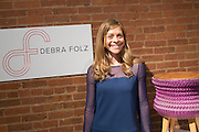 Designer Debra Folz, beside a stool with pleated fabric apron.