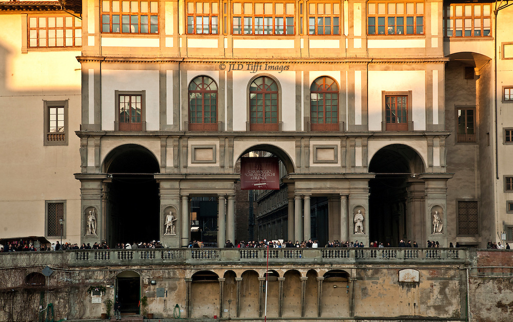 Telephoto view of the Uffizi Gallery river facade from across the Arno River, showing the late afternoon crowds, seeming like a row of ants creeping along the sidewalk behind the river bank balustrade.
