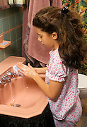 Young girl in pajamas washing her hands at bedtime.
