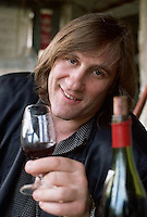March 1991, Bourgival, France --- French movie star Gerard Depardieu drinks a glass of wine at his winery.  Bourgival, France. --- Image by © Owen Franken/CORBIS