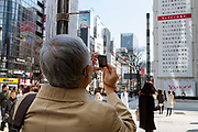 A Japanese man takes a photo of a large billboard on the side of the Sony Building in Ginza marks the sixth anniversary of the March 11th 2011 earthquake and tsunami in Tohoku. Ginza, Tokyo, Japan. Friday March 10th 2017 The billboard was created by Yahoo and shows the asks passers by to remember the disaster and the nearly 16,000 people who died. the line marked in red shows the maximum height of the tsunami (16.7 metres at Ofunato in Miyagi prefecture. The billboard is on display until March 12th.