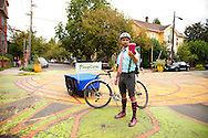 """Jed Lazar, owner of Soupcycle, delivering soup in SE Portland, Oregon.  With a monthly, """"Soupscription,"""" subscribers are entitled to one delivery per week which includes a quart of freshly made soup, salad and bread.  Each week Soupcycle makes three kinds of soup - vegan, vegetarian, and meat - that customers may choose from.  He delivers them by a bicycle that has been fitted with a trailer that can carry up to 215 pounds."""