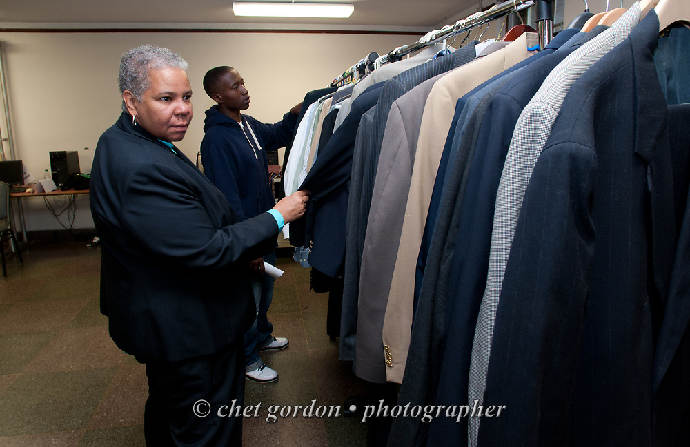 Newburgh City Councilwoman Gay Lee examines a rack of men's suits suits during the Newburgh Job Fair at the Newburgh Armory Unity Center in Newburgh, NY on Tuesday June 16, 2015. Councilwoman Lee, a Democratic candidate for mayor of Orange County's largest city, is a co-sponsor of the daylong event.  © Chet Gordon • Photographer