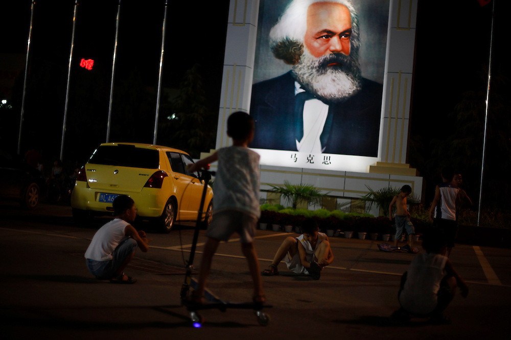 Children play next to a large painting in the likeness of Communist ideologist Karl Marx in the model village of Nan Jie Cun, China, China, Tuesday, Aug. 25, 2009. Nan Jie Cun village in central China's Henan province advertises itself as a commune which continues to adhere to the communist teachings of Mao Zedong, who founded the People's Republic 60 years ago. The village's industries are collectively owned. Workers receive bonds, instead of currency, and housing and healthcare are free. They sing revolutionary songs and march to work in lines. Despite being out of step with the rest of today's China, the village's industries are a success, and more than 7,000 migrants have requested to work at Nan Jie Cun.