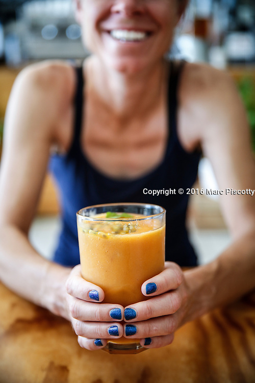 SHOT 12/9/16 8:29:53 AM - Missy Simpson of Denver, Co. flashes a smile while holding a Tropical Breeze breakfast smoothie at Del Cielo Tulum Bistro Tropical. It is a restaurant serving breakfast, lunch and dinner in Tulum, Mexico. Tulum is located in the Mayan Riviera and along the east coast of the Yucatán Peninsula on the Caribbean Sea in the state of Quintana Roo, Mexico. (Photo by Marc Piscotty / © 2016)