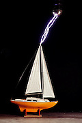 Simulated lightning strike to a sailboat model in lab. Institution för Hopspänningsforkning, Husbyborg, Uppsala, Sweden. Engineer - Eric Löfberg (1991).Lightning occurs when a large electrical charge builds up in a cloud, probably due to the friction of water and ice particles. The charge induces an opposite charge on the ground, and a few leader electrons travel to the ground. When one makes contact, there is a huge backflow of energy up the path of the electron. This produces a bright flash of light, and temperatures of up to 30,000 degrees Celsius.