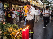 18 AUGUST 2015 - BANGKOK, THAILAND: A man brings a marigold garland to a makeshift memorial in front of Erawan Shrine, which was damaged by a bomb Monday night. An explosion at Erawan Shrine, a popular tourist attraction and important religious shrine in the heart of the Bangkok shopping district, killed at least 20 people and injured more than 120 others, including foreign tourists, during the Monday evening rush hour. Twelve of the dead were killed at the scene. Thai police said an Improvised Explosive Device (IED) was detonated at 18.55. Police said the bomb was made of more than six pounds of explosives stuffed in a pipe and wrapped with white cloth. Its destructive radius was estimated at 100 meters.    PHOTO BY JACK KURTZ