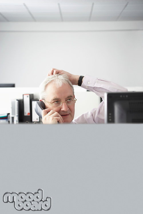 Mature businessman using telephone with hand on head in office cubicle