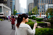 Woman taking a photograph with her mobile phone close to the Imperial Castle Garden in Tokyo. Tokyo has 13.01 million inhabitans, is the Japanese capital and the largest city in Japan. Tokyo, Japan, 20.10 2010.