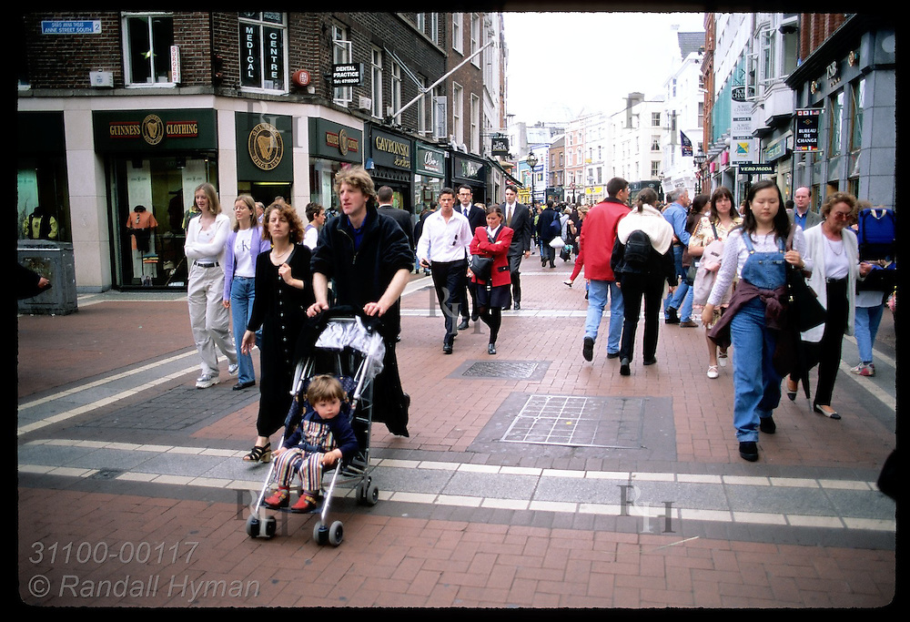 Pedestrians pass rows of shops on busy Grafton Street, popular walking mall in downtown Dublin. Ireland