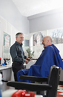 Barber and man in barbers shop smiling