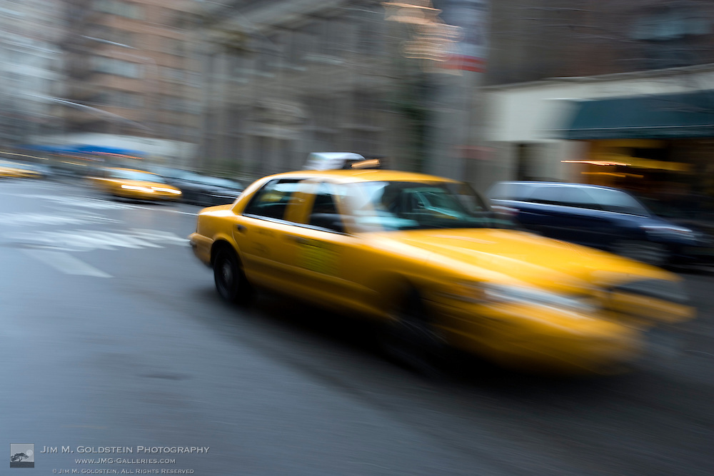 A taxi cab rushes through downtown New York city