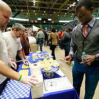 Thomas Wells | BUY AT PHOTOS.DJOURNAL.COM<br /> Brett Murphy, left, serves Howard Belk a sample of one of their dishes from Amsterdam Deli during Thursday's Taste of Tupelo at the BancorpSouth Arena.