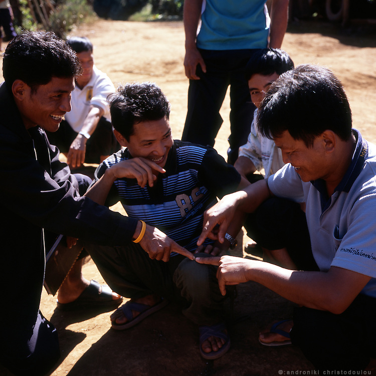 Men playing a game at the Akha village Huei Naam Kun that is located in the mountains near Chiang Rai.