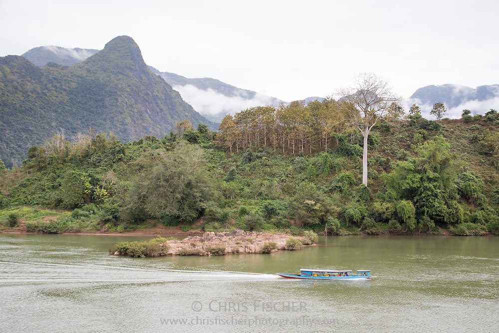 The beautiful landscape along the Nam Ou (Ou River) in Luang Prabang Province, Laos. A boat heads down river while beyond the fog drifts through the mountains.
