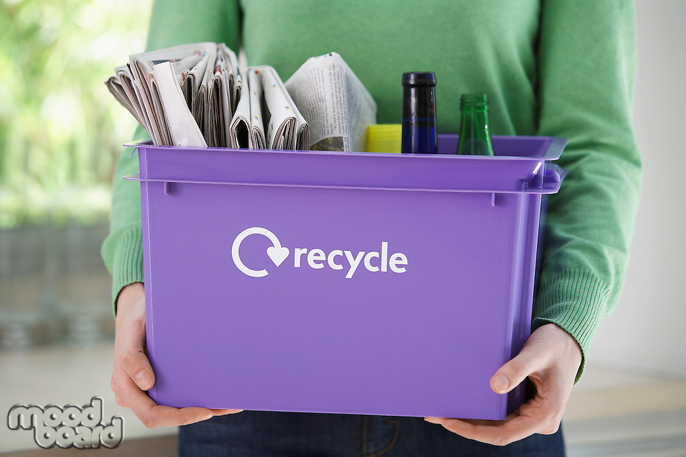 Woman holding recycle container mid section