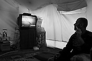 From his tent in Reyhanli camp, a Syrian refugee watches Addounia TV, a pro-Assad regime news station with disbelief.  The channel has supported the government's stance on the events in the country since the start of the revolution in March 2012. Reyhanli, Hatay, Turkey, 16th March 2012