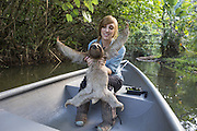 Brown-throated Three-toed Sloth <br /> Bradypus variegatus<br /> Rebecca Cliff, sloth biologist, holding sloth wearing sloth backpack while traveling in boat to release site<br /> Aviarios Sloth Sanctuary, Costa Rica<br /> *Model release available