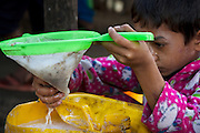 A moment in the process, where the possible impurities present in the sap are strained out. At Ka Myaw Gyi village in the outskirts of Dawei, Myanmar.