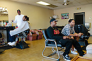 Rap producer Mike Will plays a video game with Baebae Overall (right) at Strictly Platinum Barber Shop in Marietta, Georgia October 4, 2012.