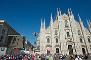 Contador raises his hands in victory after crossing the TT finish--shown live on big screens in front of Milan's Duomo.
