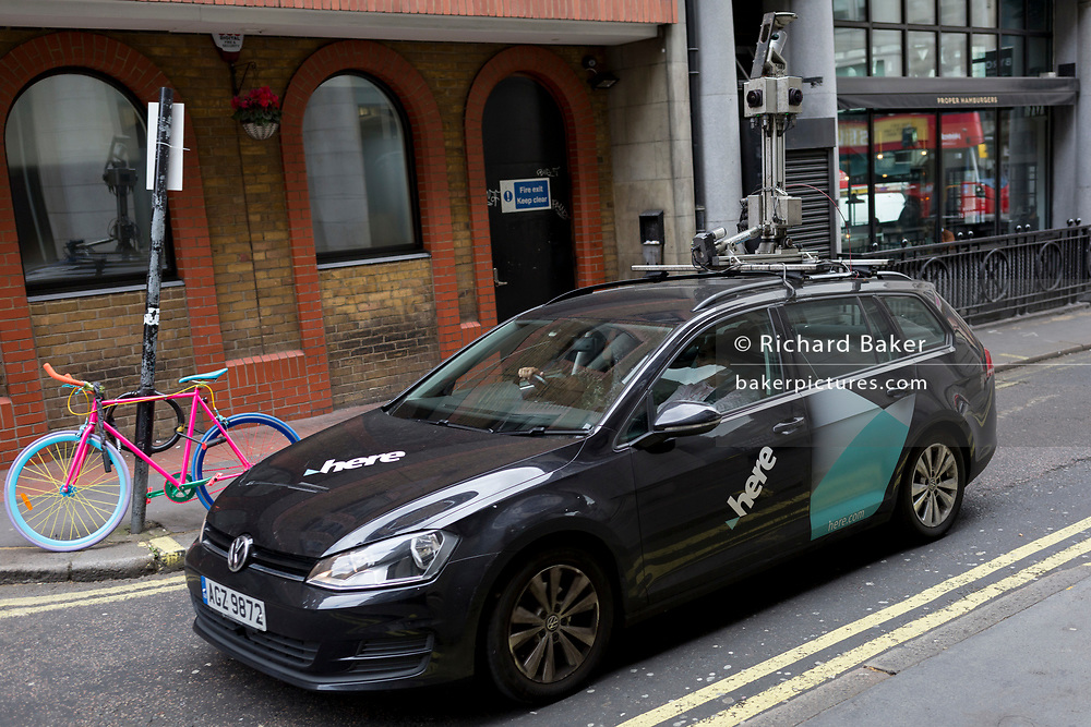 A data car with 'Here Technologies' and with roof-mounted cameras, drives past a multi-coloured bike locked to a post in a sidestreet in London's West End, on 29th April 2019, in London, England. From autonomous driving, to the Internet of Things, 'Here' are building the future of location technology. Starting in 1985, they began with digital mapping mapping and in-car navigation systems. Over the next three decades, as NAVTEQ and Nokia, we've built a legacy in mapping technology. They now employ 8,000 workers.