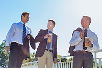 Businessmen drinking coffee while walking and talking during break