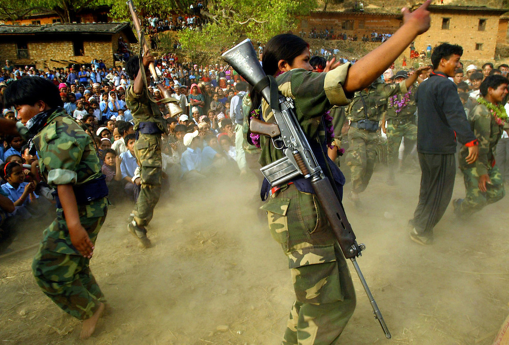 Armed Troops from the 2nd Battalion dance alongside villagers after descending from the mountains in to the valley to take part in a cultural program and remembrance ceremony in the village of Kholagaun, in the Maoist heartland of Nepal, Thursday, April 22, 2004. Although more than 600 people have been injured in battles with the police and the street protestors, the five major political parties continue their demonstrations, demanding that King Gyanendra dismiss the government appointed by him, and allow new elections or form a government led by the major parties in the last Parliament.