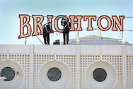 Maintenance men working high above the day trippers and tourists replace some of the 62,000 light bulbs it takes to illuminate Brighton Pier. 3 June 2015 <br /> JAMES BOARDMAN 07967642437